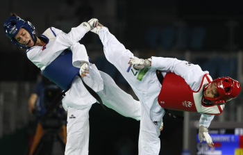 Serbia's Tijana Bogdanovic (blue) fights against Sohui Kim of South Korea during their final bout