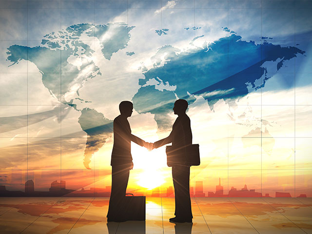 Two businessmen shake hands in front of the world map
